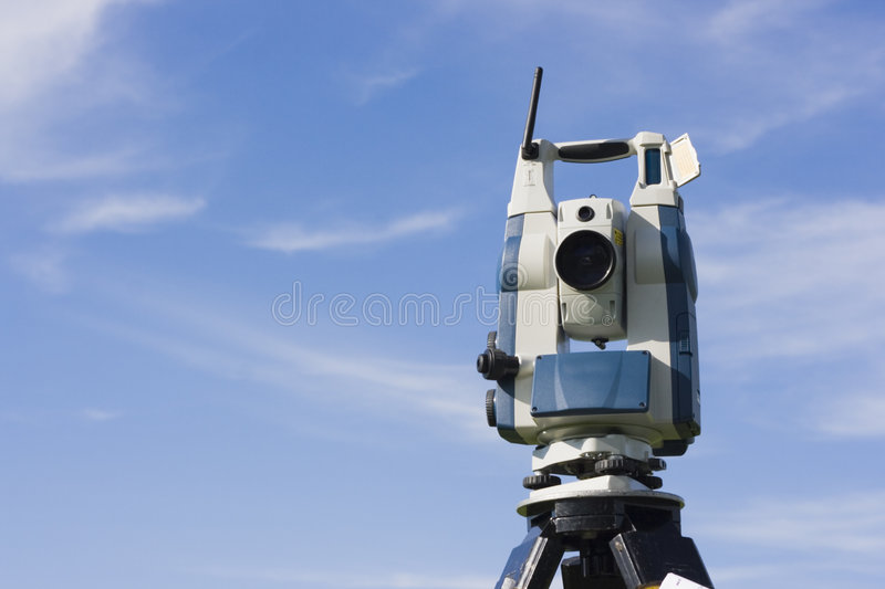 Theodolite against blue sky stock photos