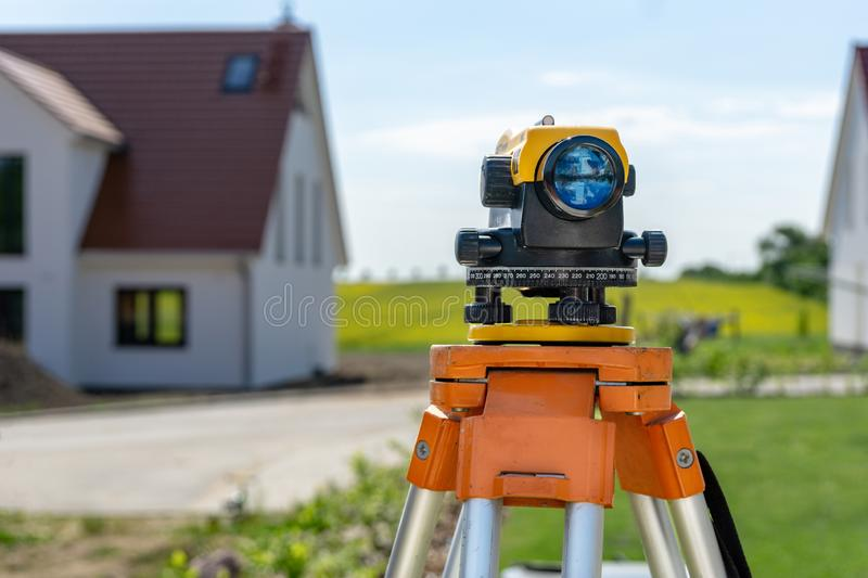 Theodolite on tripod on yard. A theodolite on a yard for a land survey stock image