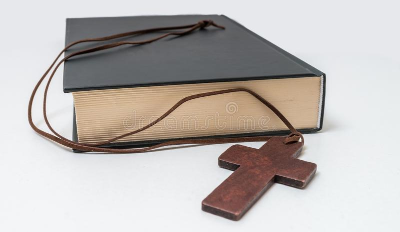 Theology concept. Bible book and brown crucifix on necklace.  royalty free stock images
