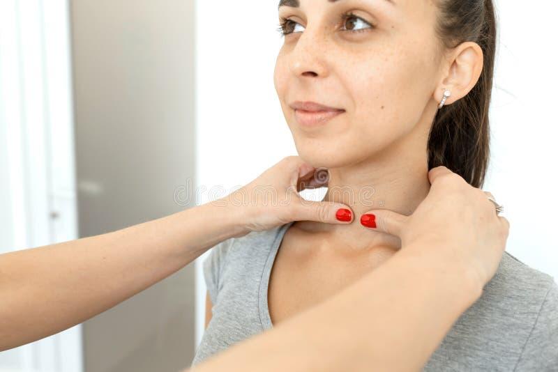 Therapeut überprüft einen Patienten des jungen Mädchens Kehle im Hals, Schilddrüsenerweiterung stockbilder