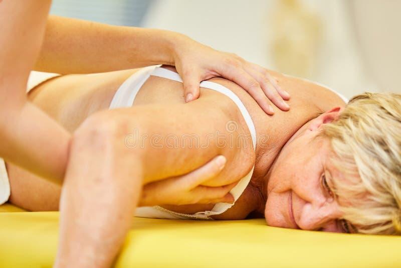 Therapeut behandelt die Schulterschmerz mit Chiropraktik stockfoto