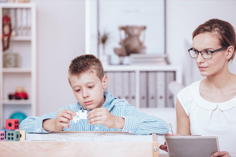 Therapeut belangrijke therapie met jongen stock foto