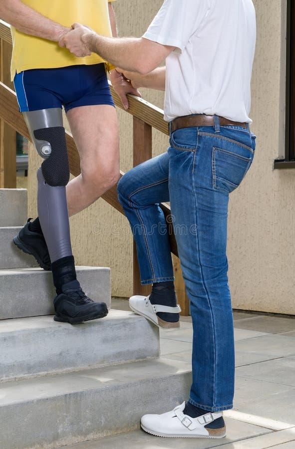 Therapeut bijwonend geamputeerde met been op treden royalty-vrije stock foto
