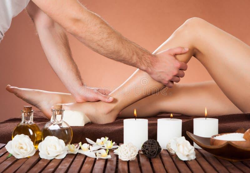 Therapeut, der das Bein des Kunden am Schönheitsbadekurort massiert stockfoto