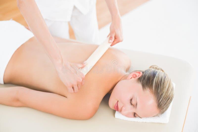 Therapeut, der die Rückseite der Frau in der Badekurortmitte einwächst lizenzfreies stockbild