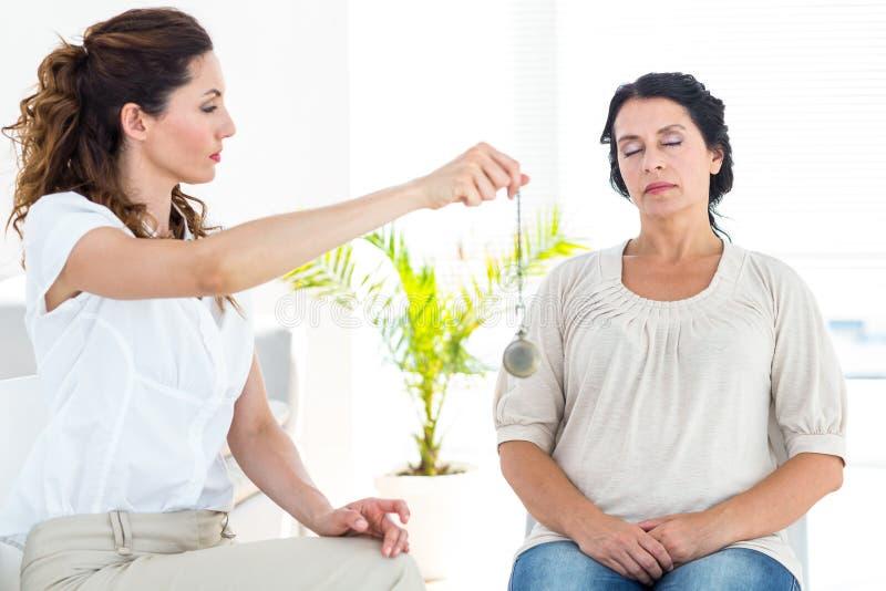 Therapeut, der ihren Patienten hypnotisiert lizenzfreies stockbild