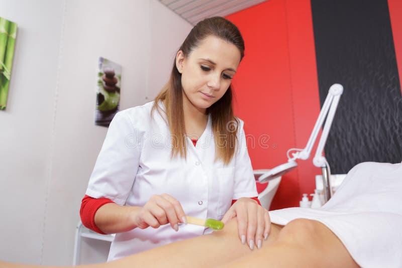 Therapeut, der der jungen Frau epilation Behandlung gibt lizenzfreie stockbilder