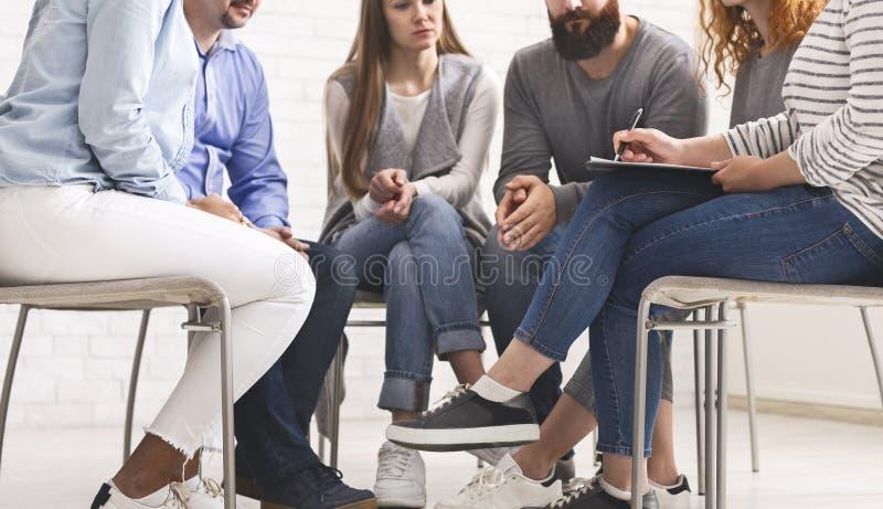 Therapeut, der mit einer Rehabilitationsgruppe an der Therapie-Sitzung spricht stockbild