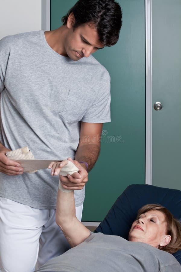 Therapeut, der Verband auf der Hand anwendet lizenzfreie stockfotos
