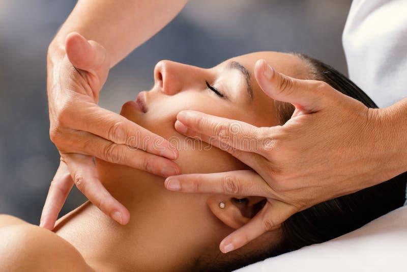 Therapeut, der weibliches Gesicht massiert stockfoto