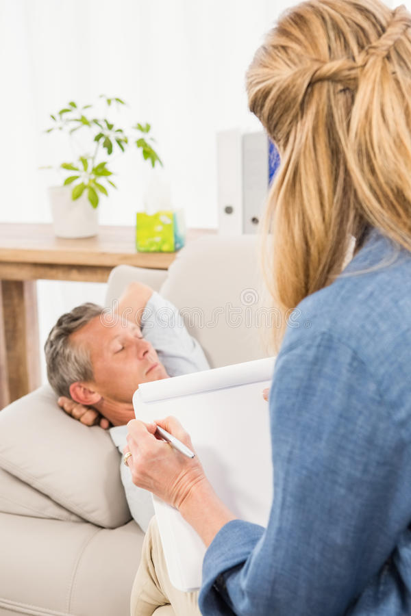 Therapeut die aan mannelijke patiënt luisteren en nota's nemen stock foto's