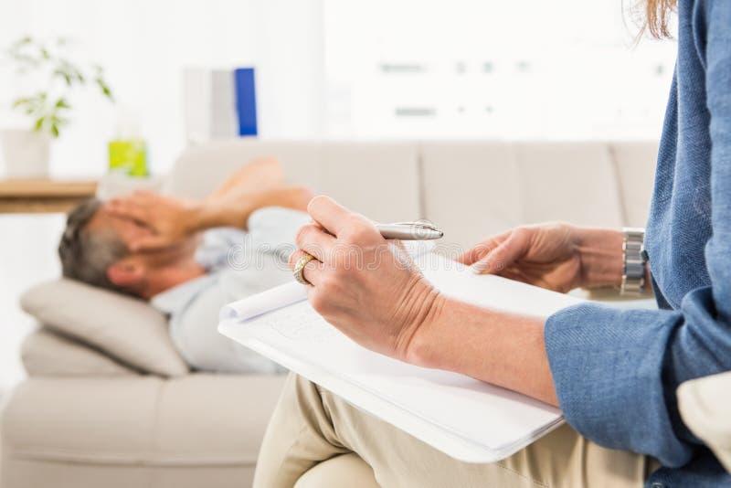 Therapeut die aan mannelijke patiënt luisteren en nota's nemen royalty-vrije stock fotografie