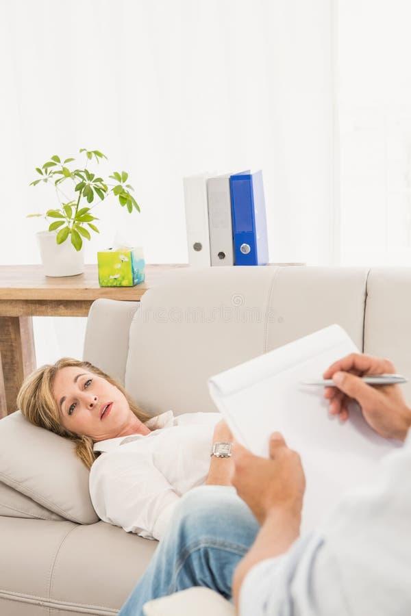 Therapeut die aan vrouwelijke patiënt luisteren en nota's nemen royalty-vrije stock afbeeldingen