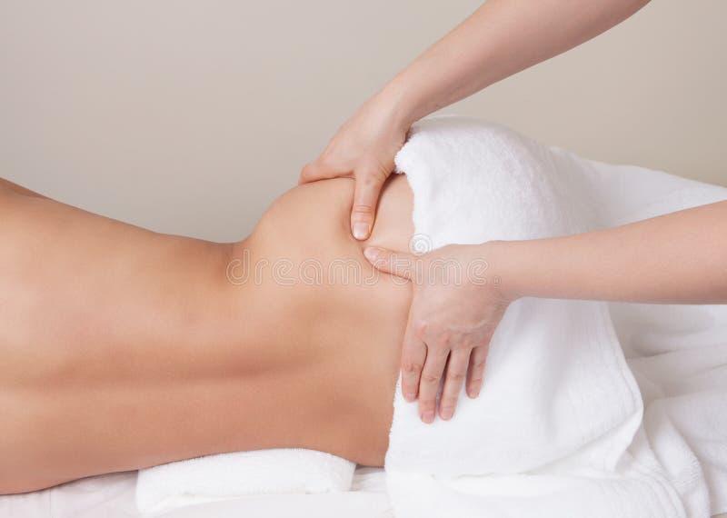 Therapeut die de massage van het drukpunt op de heup van een vrouw doen stock afbeelding