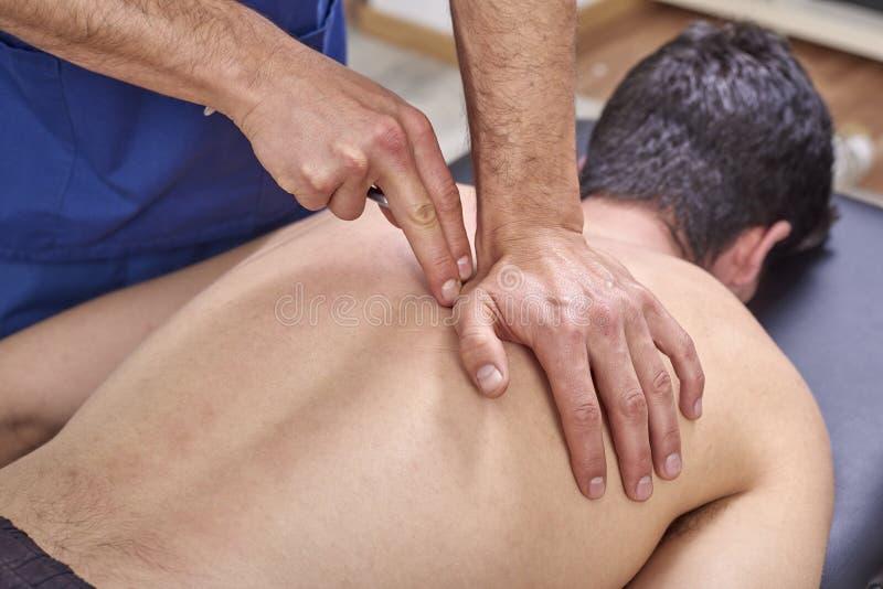 Therapeut die diacutaneous Fibrolysis, van de haken doen die behandeling op man& x27 helen; s rug Alternatieve geneeskunde Chirop stock foto