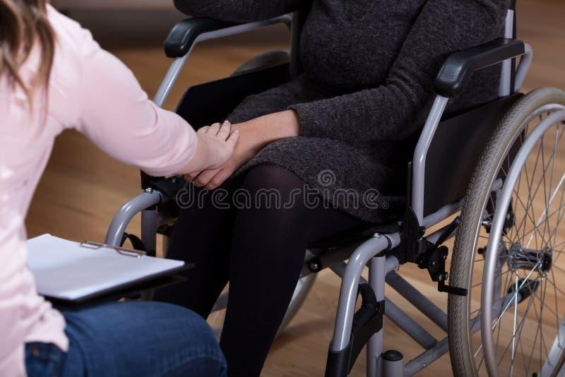 Therapeut die gehandicapte vrouw troosten stock afbeelding