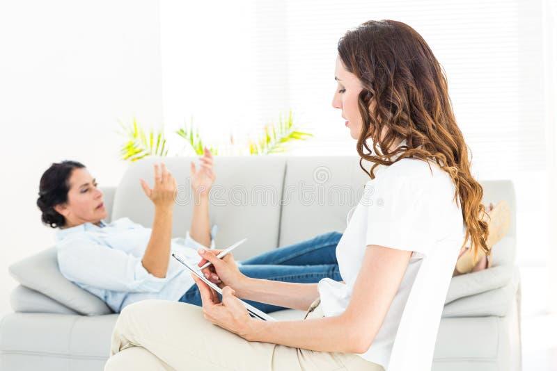 Therapeut die haar patiënt en nota's nemen luisteren stock afbeelding