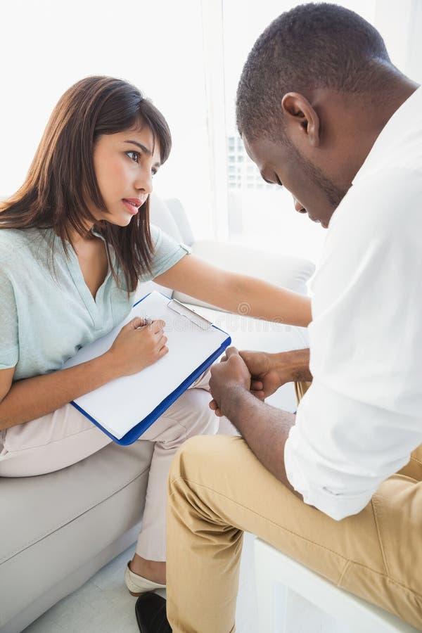 Therapeut die haar verstoorde patiënt troosten stock fotografie