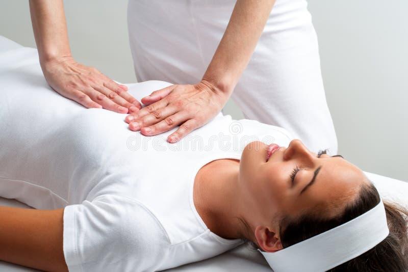 Therapeut die met handen op de borst van de vrouw bij reikizitting drukken stock afbeeldingen