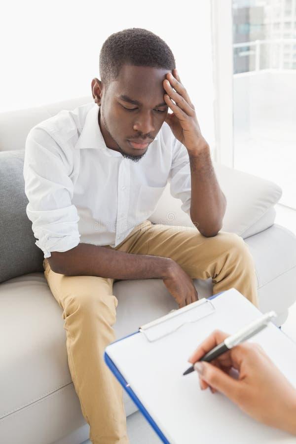 Therapeut die nota's over haar gedeprimeerde patiënt nemen royalty-vrije stock foto