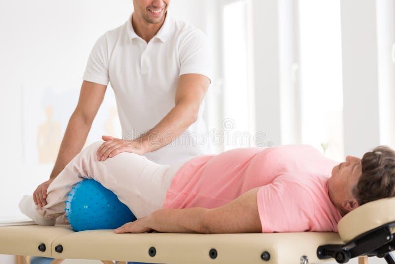 Therapeut die oude vrouw masseren stock afbeeldingen