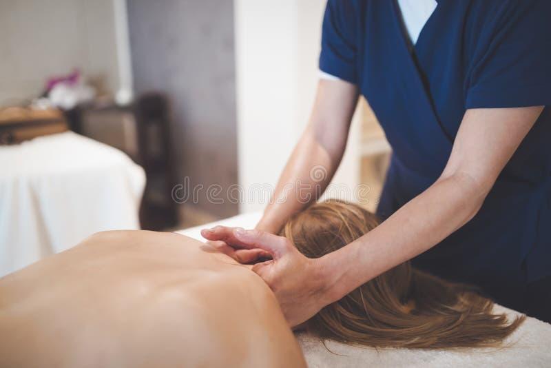 Therapeut die patiënt masseren in wellness spa stock afbeelding
