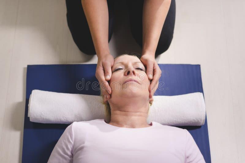 Therapeut die reikitherapie doet aan hogere vrouw stock foto