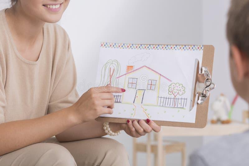 Therapeut die tekening van huis tonen stock afbeeldingen