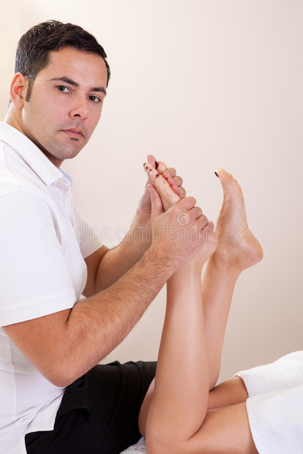 Therapeut die voetmassage doet stock foto's