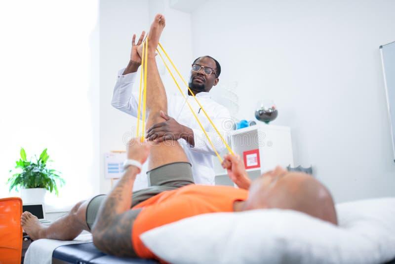 Therapeut die zijn geduldig het uitrekken zich been na opleiding helpen stock afbeelding