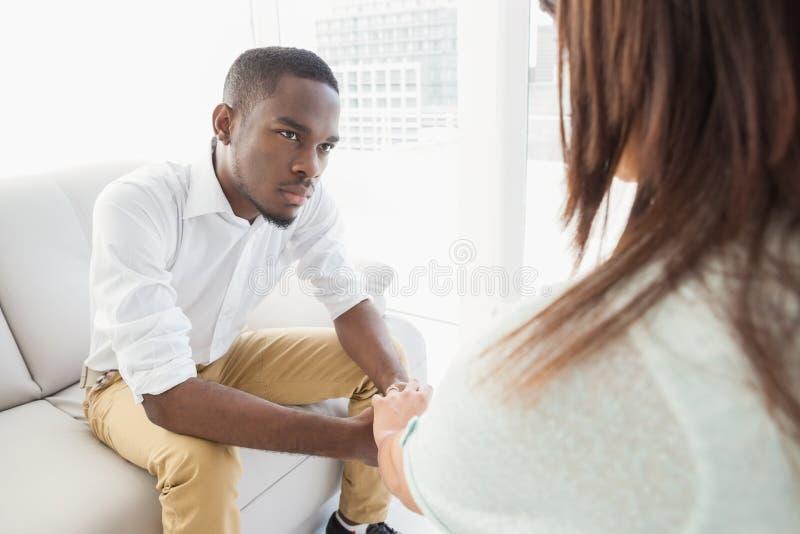 Therapeut die zijn luisterpatiënt adviseren stock afbeeldingen