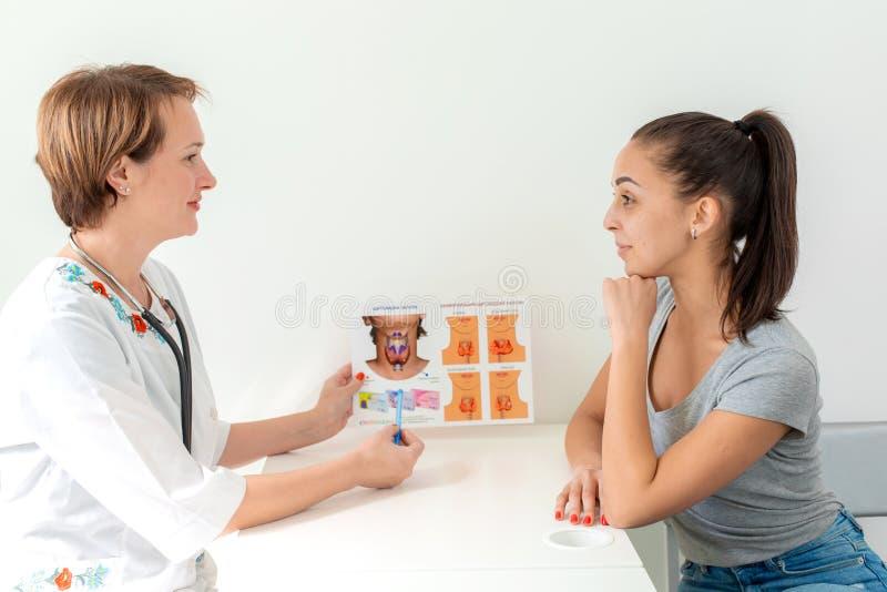 Therapeut erklärt einem jungen Patienten über Schilddrüse und die Showbilder stockfoto