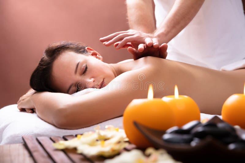 Therapeut Giving Back Massage zur jungen Frau stockfoto