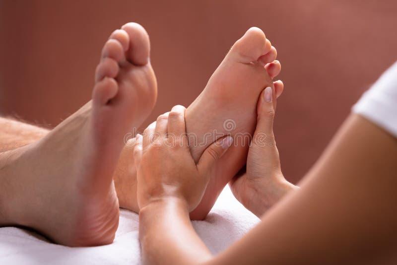 Therapeut Giving Foot Massage aan de Mens stock afbeeldingen