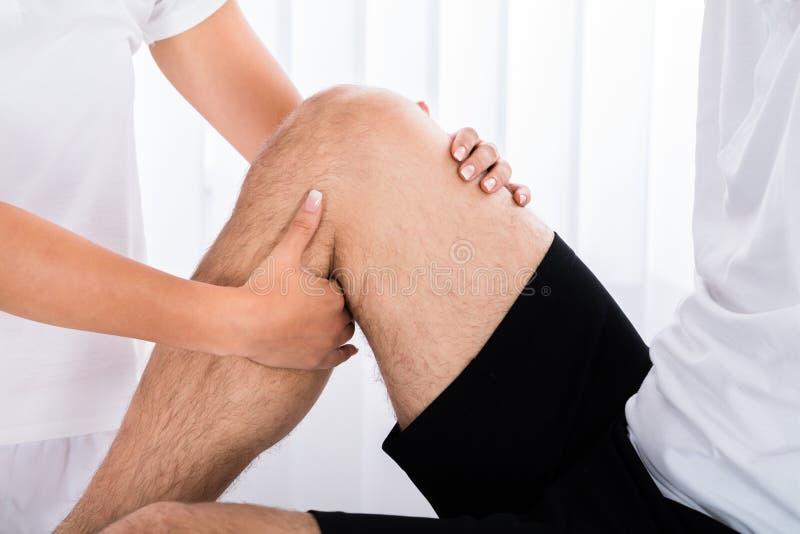 Therapeut-Hand Massaging Man-` s Bein im Badekurort stockfotos