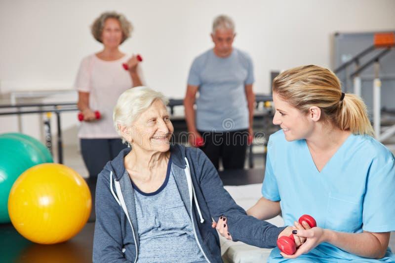 Therapeut stützt ältere Frau im Dummkopftraining stockfotografie