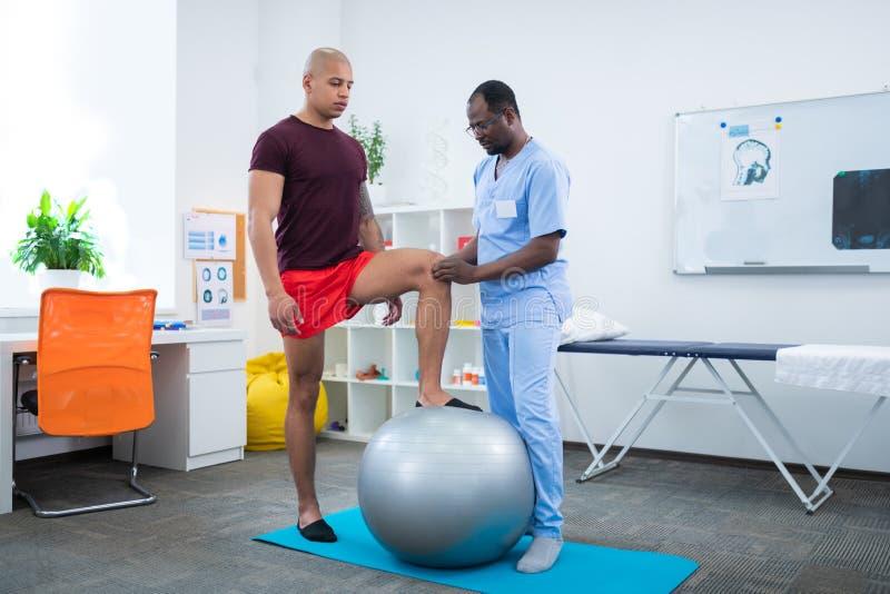Therapeut wat betreft knie die van sportman zich dichtbij geschikte bal bevindt stock foto