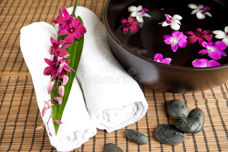 Therapie mit Orchideen und heißen Steinen stockfoto