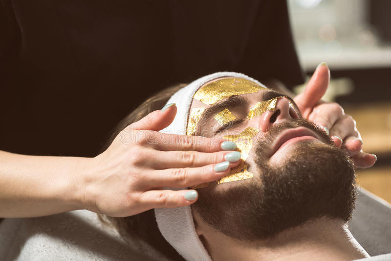 Therapie van het mensen` s de gouden masker bij schoonheidsspecialist ` s royalty-vrije stock foto