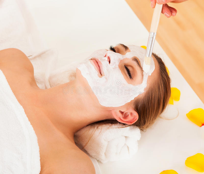 Therapist applying a face mask. To the face of a beautiful young blonde woman using a cosmetic brush royalty free stock photos