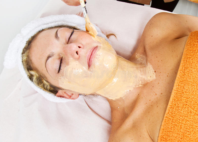 Therapist applying a face mask to a beautiful young woman. In a spa using a cosmetics brush stock photography