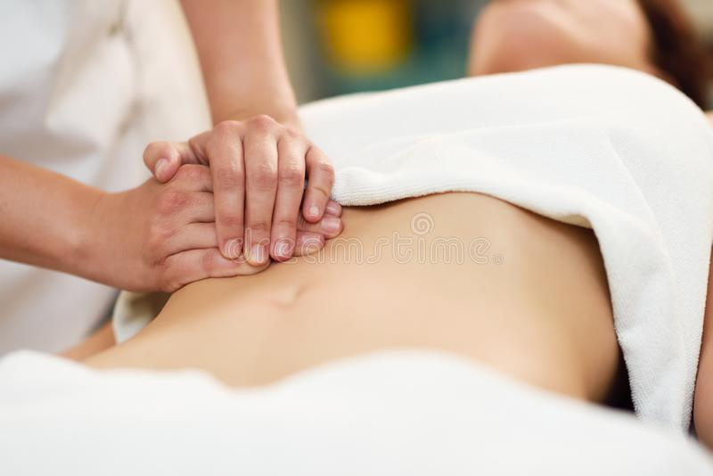 Therapist applying pressure on belly. Hands massaging woman abdomen. Therapist applying pressure on belly. Woman receiving massage at spa salon. Hands massaging stock photos