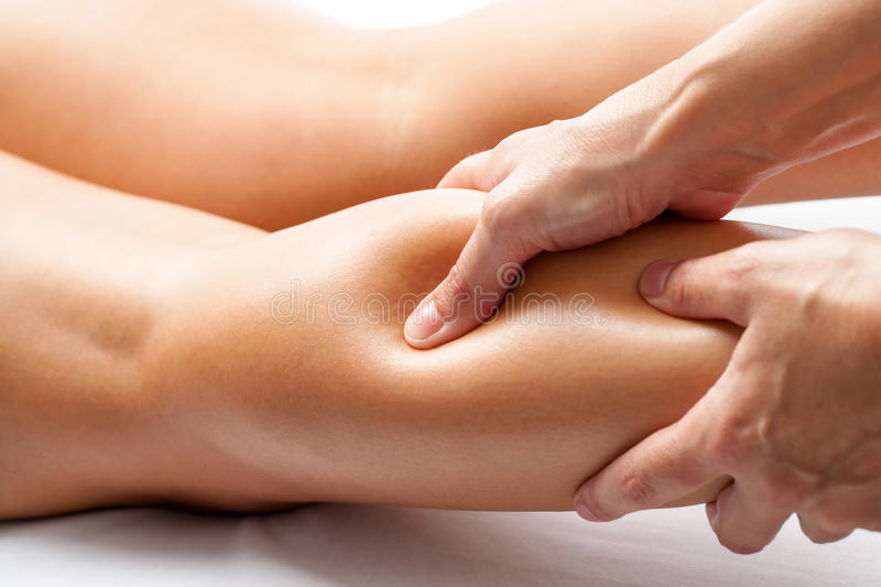 Therapist applying pressure with thumb on female calf muscle. royalty free stock photography