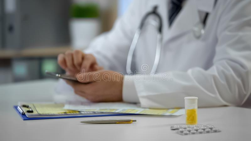Therapist checking medical records on phone, online consultation and prescribing stock photo