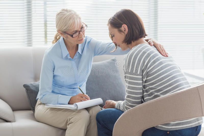 Therapist comforting woman royalty free stock image