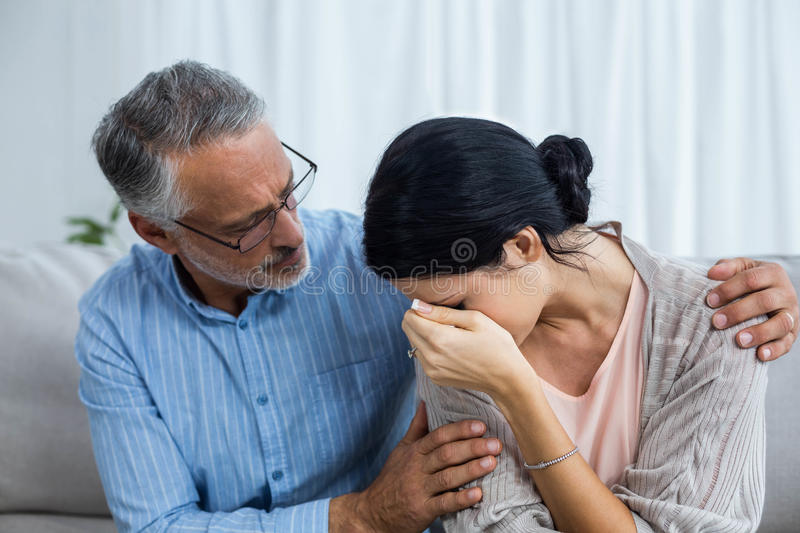 Therapist consoling a woman. Therapist consoling a women at home royalty free stock photography