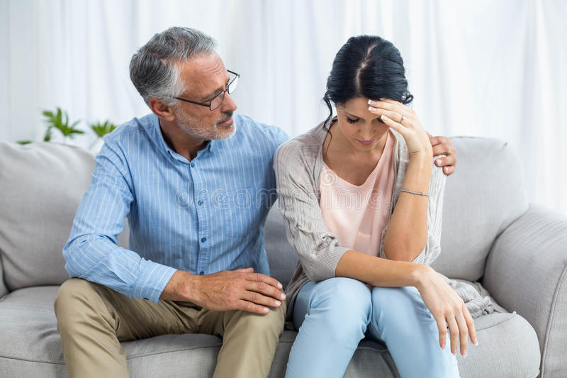 Therapist consoling a woman. Therapist consoling a women at home stock image
