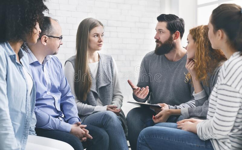 Therapist consulting patients of rehab group at therapy session stock photography