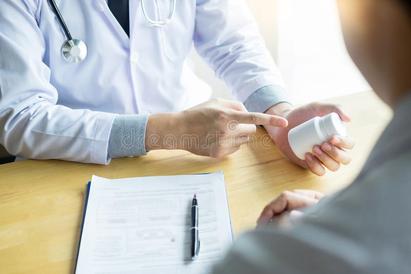 Therapist consulting to patient male patient about pills writing his medical prescription drug in the office royalty free stock image