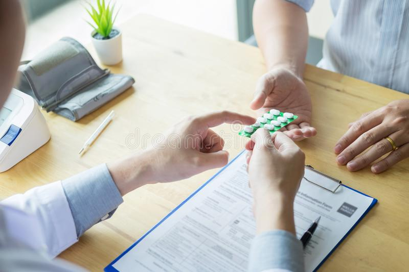 Therapist consulting to patient male patient about pills writing his medical prescription drug in the office.  royalty free stock image